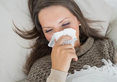 sick woman lying on sofa and