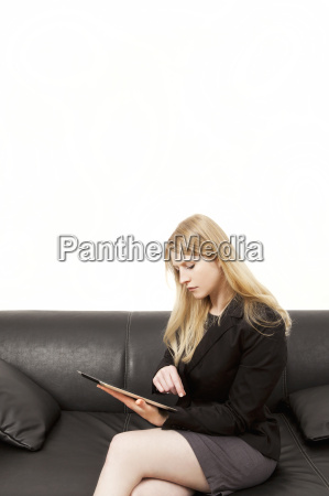 businesswoman on couch works with tablet
