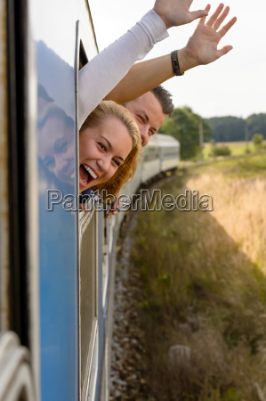 couple screaming out train window waving