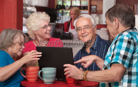 seniors having fun with computer in