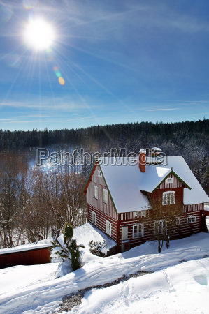 wooden old red cottage in winter