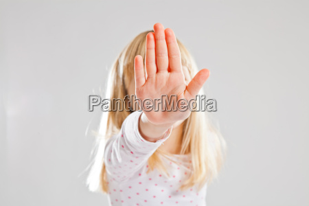 young girl showing stop hand sign