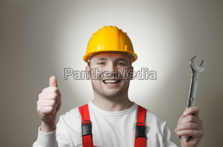 smiling young worker with a wrench