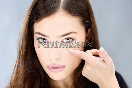 woman hold contact lens on finger