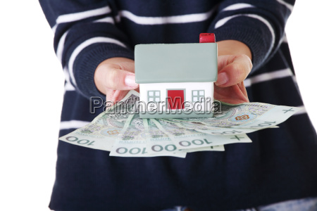 woman holding pln bills and house