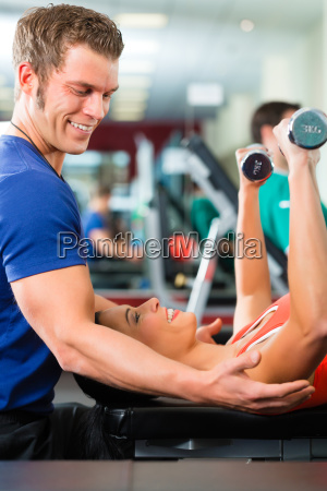 trainer and woman in gym with