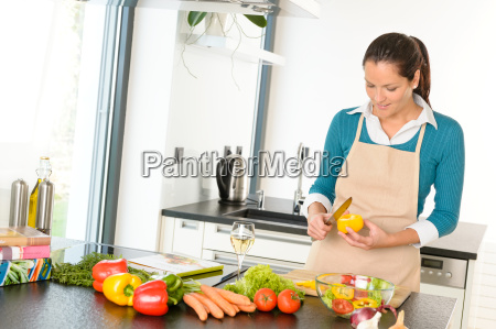 young woman cutting vegetables kitchen preparing