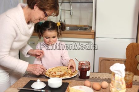 mother preparing crepes with little girl