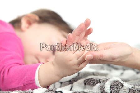 baby sleeping takes the hand of