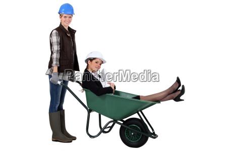 worker pushing boss around in wheelbarrow