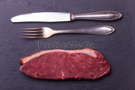raw steak and cutlery on slate