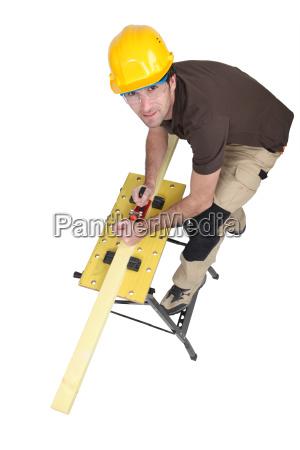 carpenter sharpening lumber isolated on white