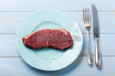 raw steak on a blue plate