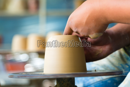 potter works on a potters wheel