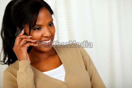 beautiful black woman conversing on mobile