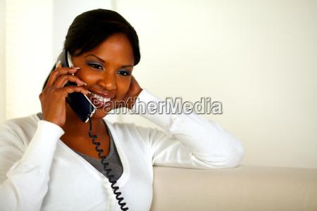 smiling black woman talking on phone