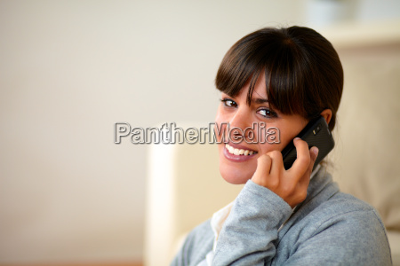 friendly young woman speaking on cellphone