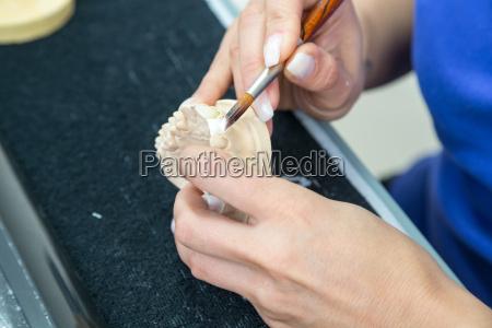 dental technician carries ceramic on dentures