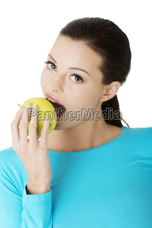 attractive young woman eating green apple