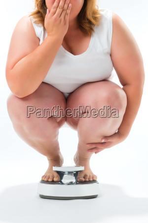 thickness young woman squatting on scales
