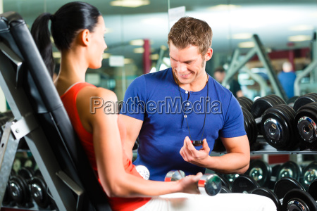 trainer and woman in fitness studio