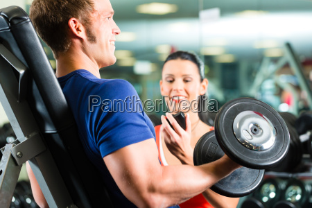 trainer and man with dumbbells in