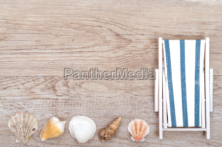 lounger and shells on weathered wood