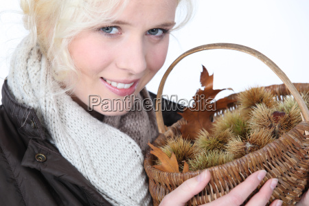 young woman holding basket of chestnuts