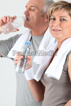 senior couple drinking water after training