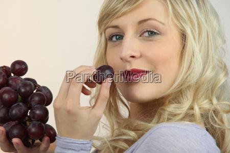 platinum blonde eating red grapes