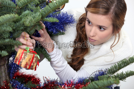 girl hanging gift from christmas tree