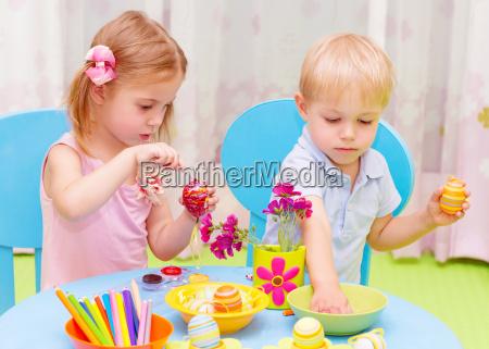 children paint easter eggs