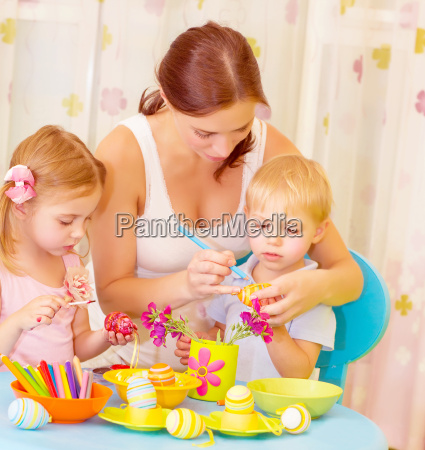 children with mother paint eggs