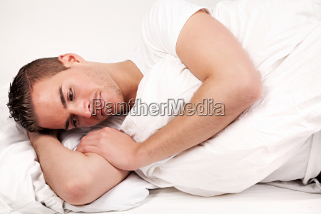 beautiful young man lying in bed