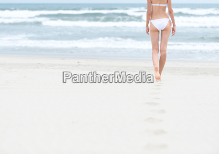 slim girl in white swimsuit walking