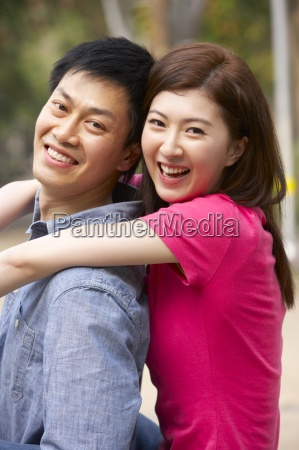 young chinese couple relaxing in park
