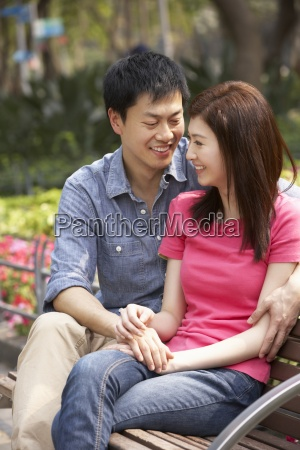 young chinese couple relaxing on park