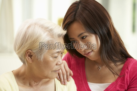 unhappy chinese mother being comforted by
