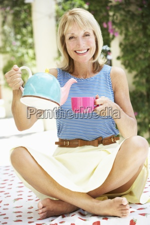 senior woman pouring cup of tea