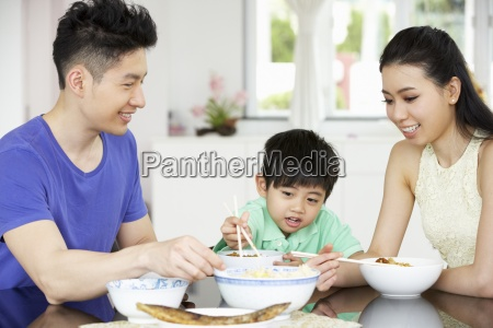 chinese family sitting at home eating