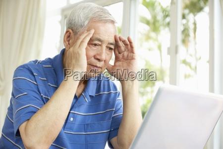 worried senior chinese man sitting at