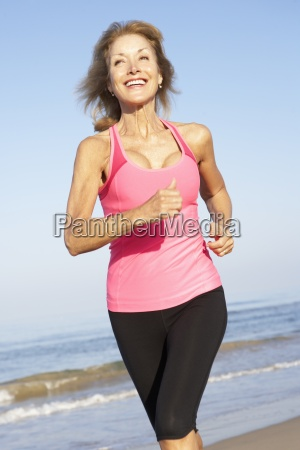 senior woman exercising on beach