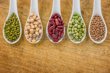 various legumes on porcelain spoons