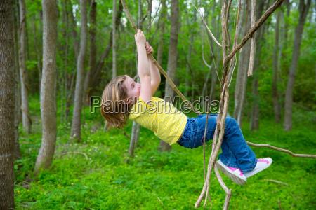 girls playing hanging in lianas at