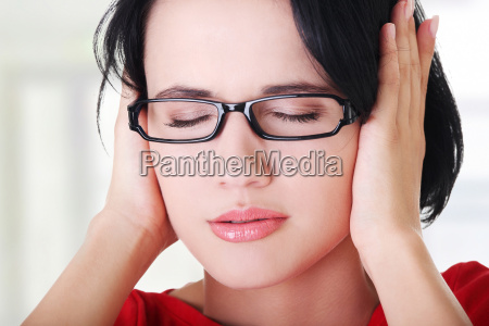 frustrated young woman holding her ears