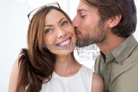 man with facial hair kissing pretty