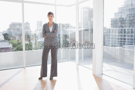 businesswoman standing in bright office with