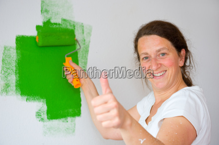 woman with paint roller and thumb