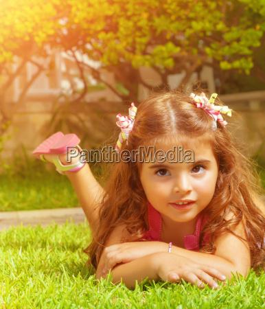 little girl lying down on green