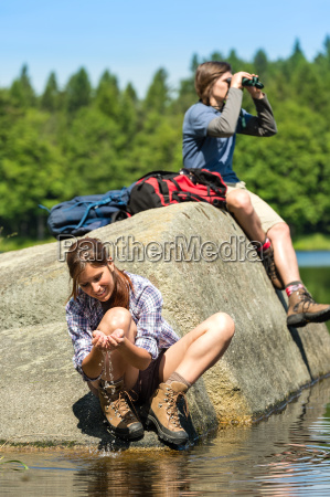 teenagers resting and birdwatching by lake